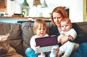 Dig Yourself Out Of Debt, Mother with two children on an iPad sitting on a couch