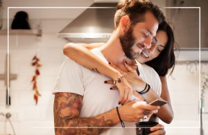 A couple in their kitchen, smiling at a phone together.