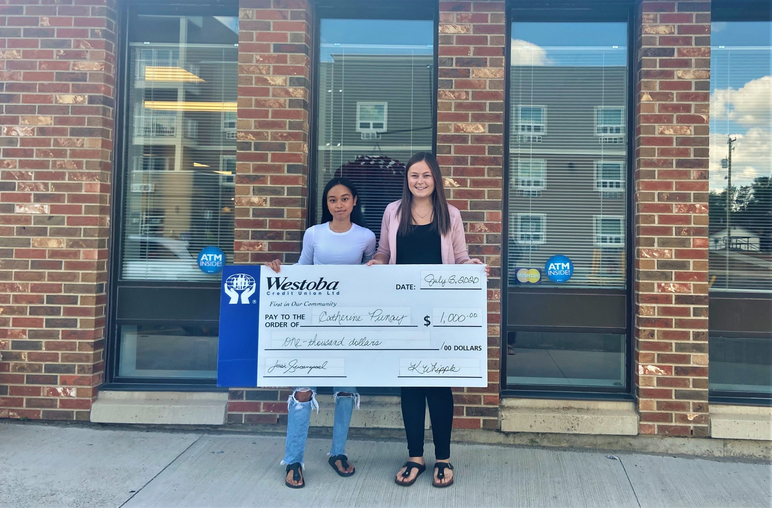 On the left, our student bursary winner recieves her cheque from a Westoba employee