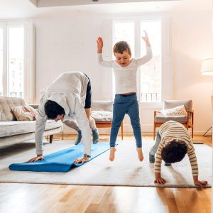 Dad exercising with two kids